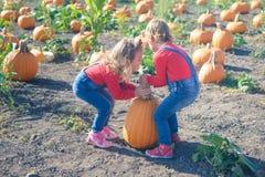 2 маленькой девочки нося тыкву на заплату поля Стоковая Фотография RF