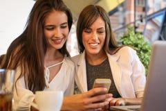 2 маленькой девочки сидя в кафе используя умный телефон Показ девушки Стоковые Изображения