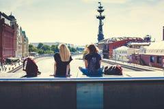 2 маленькой девочки сидя на мосте над рекой Москвы с целью Питера большой, Krasny Oktyabr и Muzeon паркуют стоковое фото rf