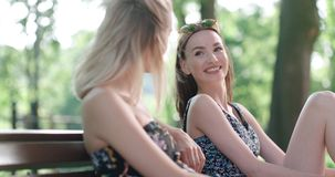 2 маленькой девочки сидя на стенде в парке наслаждаясь летом и беседовать Стоковое Изображение