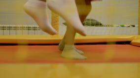 2 маленькой девочки скача на желтый батут, ноги конца-вверх, в решетке предпосылки акции видеоматериалы
