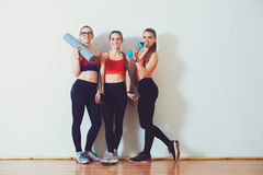 3 маленькой девочки фитнеса в sportswear стоя против стены в спортзале фитнеса Девушки усмехаясь и смотря к камере Стоковое фото RF