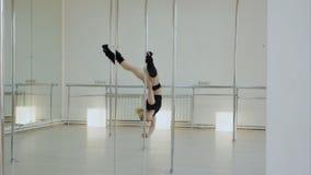 Маловероятный танцор поляка делает разделение пока виды вверх ногами на опоре в студии Стоковое фото RF