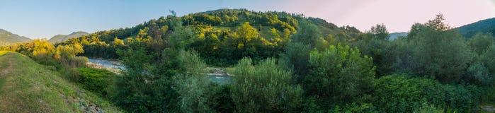 Малое быстрое река на фоне больших зеленых холмов и гор с деревьями Стоковая Фотография RF