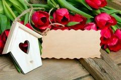 Малое деревянное украшение дома птицы с сердцем, букетом тюльпана и чистым листом бумаги Стоковая Фотография RF