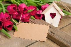Малое деревянное украшение дома птицы с сердцем, букетом тюльпана и чистым листом бумаги Стоковые Изображения RF