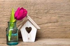 Малое деревянное украшение дома птицы с сердцем и розовым букетом тюльпана Стоковое Изображение