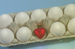 Малое красное сердце в раковине белого яичка на голубой предпосылке Стоковое фото RF