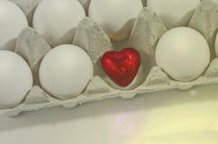 Малое красное сердце в раковине белого яичка на голубой предпосылке Стоковое Фото
