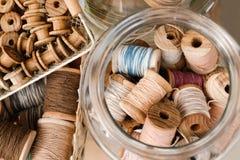 Малые деревянные катушки в корзине и большие катушки с красочными потоками в стеклянном опарнике стоковое изображение rf