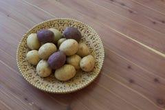 Малые красные и белые картошки в декоративном шаре расшивы березы на деревянной таблице, космосе экземпляра Стоковое Фото