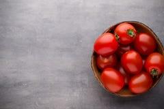 Малые томаты сливы в деревянном шаре на серой предпосылке Стоковые Фото