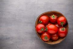 Малые томаты сливы в деревянном шаре на серой предпосылке Стоковое фото RF