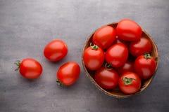 Малые томаты сливы в деревянном шаре на серой предпосылке Стоковые Фотографии RF