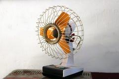 Малый античный электрический вентилятор с оранжевыми лезвиями стоковое фото