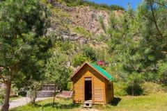 Малый деревянный дом с зеленой крышей на предпосылке высокой скалистой горы Стоковые Изображения RF