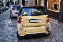 Малый желтый автомобиль города при части тела вися от ботинка Стоковые Фото