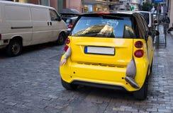 Малый желтый автомобиль города с рукой, смертной казнью через повешение ноги от ботинка Стоковое Фото