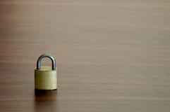 Малый ключевой замок на предпосылке деревянного стола Стоковые Изображения RF