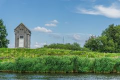 Малый коттедж выглядеть как крипта на озере в взгляде расстояния ландшафта воды стоковая фотография