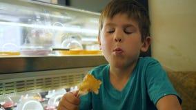 Малый мальчик в буфете ест жареный цыпленка при пластичная вилка сидя на таблице внутрь сток-видео