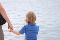Малый мальчик держит его руку ` s отца Стоковые Изображения RF