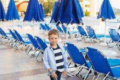 Малый мальчик стоит среди голубых зонтиков и loungers солнца дальше Стоковое Изображение