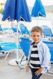 Малый мальчик стоит среди голубых зонтиков и loungers солнца дальше Стоковая Фотография