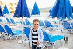 Малый мальчик стоит среди голубых зонтиков и loungers солнца дальше Стоковое Изображение RF