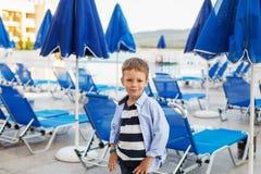 Малый мальчик стоит среди голубых зонтиков и loungers солнца дальше Стоковая Фотография RF