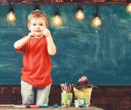 Малый мальчик стоя за таблицей Милый бокс ребенк в классе стоковые фото