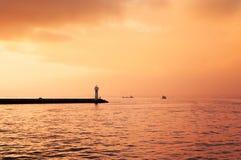 Малый маяк и красивое небо захода солнца на пасмурный день Стоковое Фото