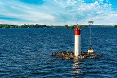 Малый маяк на реке под голубыми небесами с пушистым облаком Стоковые Изображения RF
