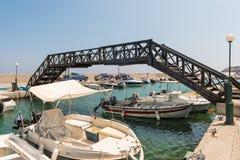Малый морской порт с причаленными рыбацкими лодками под мостом на острове Родоса, Греции Стоковые Фотографии RF
