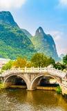Малый мост над водой и зеленые пики на Yangshuo, провинции Guangxi, Китае Стоковое Фото