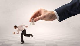 Малый предприниматель бежать далеко от сильной руки с концепцией chessman стоковые фотографии rf