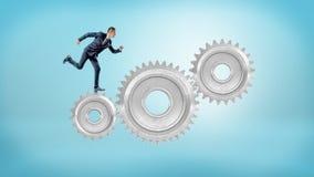 Малый предприниматель бежит на больших блокировать шестернях металла на голубой предпосылке Стоковая Фотография RF
