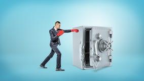 Малый предприниматель носит красные перчатки бокса и ударяет большой сломанный сейф металла Стоковые Изображения