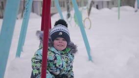 Малый ребенок играет в парке зимы Ребенок на качании зима дня солнечная Потеха и игры в свежем воздухе видеоматериал