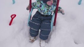 Малый ребенок играет в парке зимы Ребенок на качании зима дня солнечная Потеха и игры в свежем воздухе акции видеоматериалы