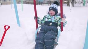 Малый ребенок играет в парке зимы Ребенок на качании зима дня солнечная Потеха и игры в свежем воздухе сток-видео