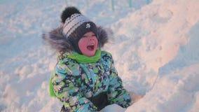 Малый ребенок играет в парке зимы с снегом зима дня солнечная Потеха и игры в свежем воздухе акции видеоматериалы