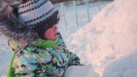 Малый ребенок играет в парке зимы с снегом зима дня солнечная Потеха и игры в свежем воздухе сток-видео