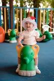 Малый ребенок сидит на зеленом наклоне в спортивную площадку и улыбки Стоковые Изображения RF