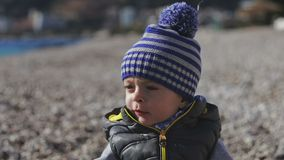 Малый ребенок усмехается в камеру и игры на пляже с камешками сток-видео