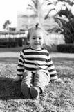 Малый ребёнок с счастливой стороной на зеленой траве barefoot Стоковые Изображения
