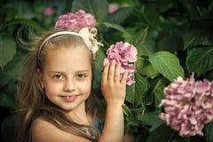 Малый ребёнок с усмехаясь стороной среди розового цветения гортензии стоковое фото