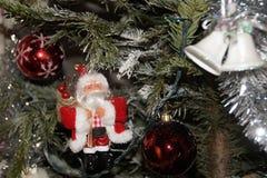 Малый Санта Клаус был повешен дальше в ели - вид спереди Стоковые Изображения