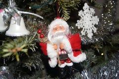 Малый Санта Клаус был повешен дальше в ели, на одном бортовом малые колоколы и с другой стороны хлопь рождества фронт Стоковое Изображение RF