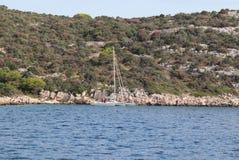 Малый тримаран плавания на предпосылке каменистого берега хорватского Ривьеры Зеленый остров Адриатического моря в Dal стоковые фотографии rf